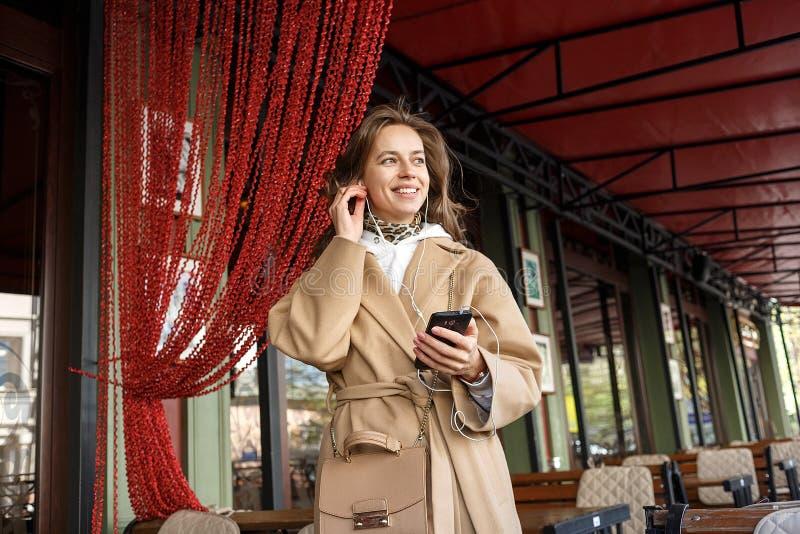 Retrato de la capa que lleva de la chica joven que escucha la música en el mirador del café con el teléfono celular de tenencia d fotos de archivo