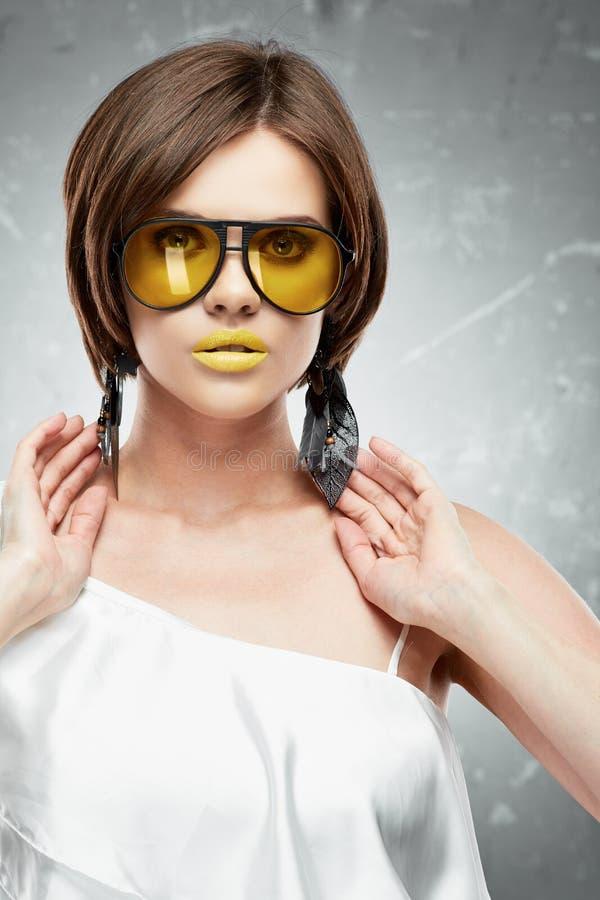 Retrato de la cara de la belleza del modelo con los vidrios de sol amarillos imagenes de archivo