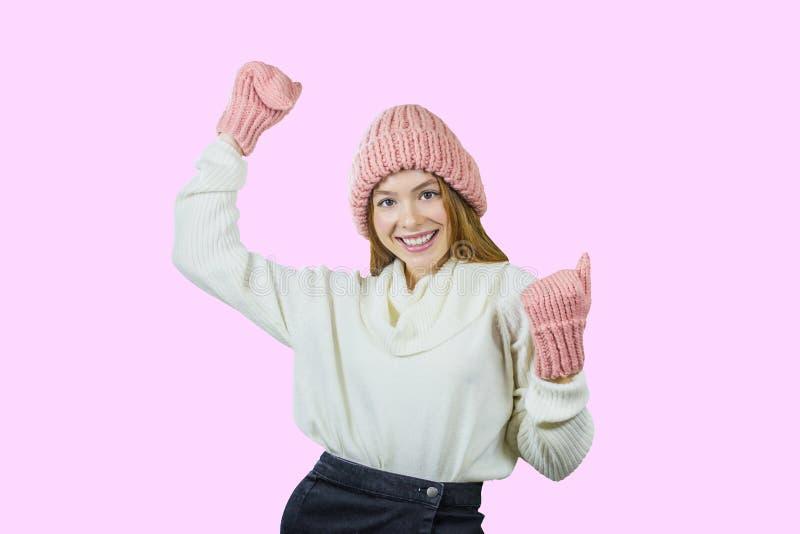 Retrato de la cara del primer de una sonrisa dentuda de una muchacha pelirroja joven que lleva un sombrero rosado y las manoplas  fotos de archivo