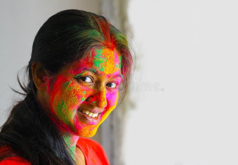 Retrato de la cara india de la chica joven pintada con los colores que sonríen con los ojos abiertos con el espacio para el texto fotografía de archivo