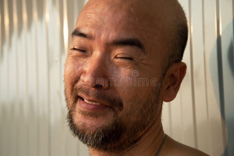 Retrato de la cara japonesa del hombre de la barba calva en la expresión divertida feliz con luz del sol natural imagen de archivo