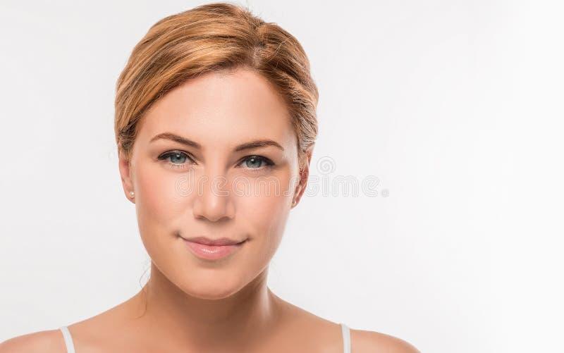 Retrato de la cara de la mujer de la belleza En cámara de mirada femenina rubia en un fondo blanco foto de archivo libre de regalías