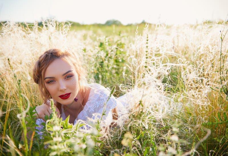 Retrato de la chica joven atractiva que miente en hierba fotografía de archivo