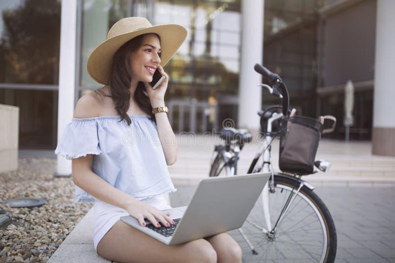 Retrato de la chica joven atractiva que usa el ordenador portátil imagen de archivo