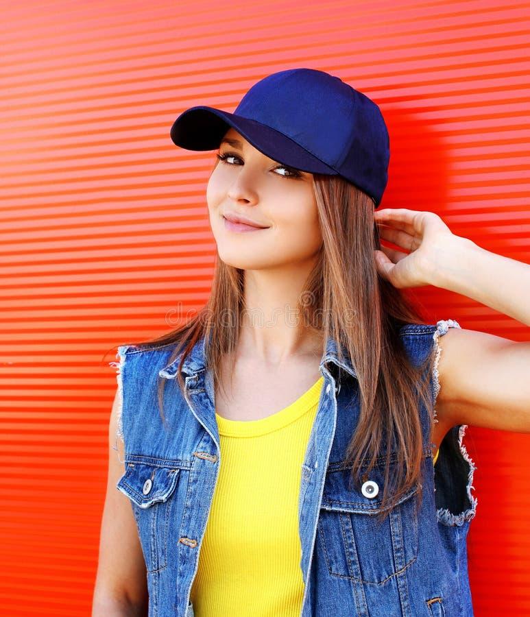 Retrato de la chica joven bastante elegante que lleva un casquillo y vaqueros foto de archivo libre de regalías