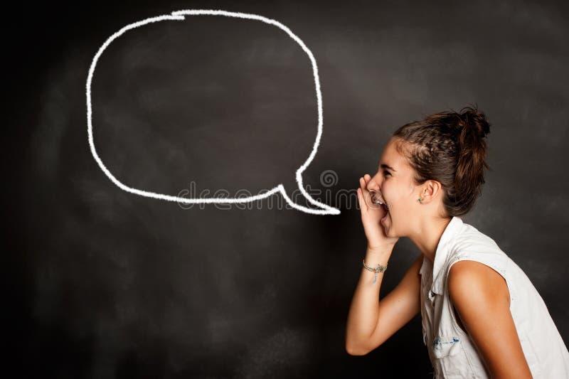 Retrato de la chica joven con la burbuja del discurso en la pizarra imagen de archivo
