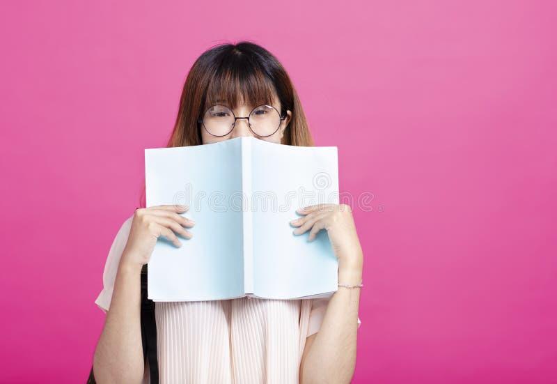 Retrato de la chica joven detrás de un libro abierto foto de archivo