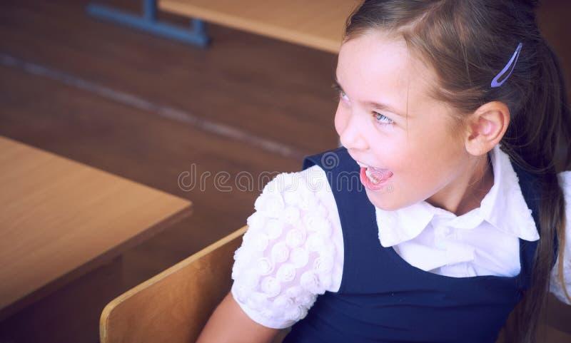 Retrato de la chica joven feliz que se sienta en la tabla en la escuela primaria Cara del primer de la colegiala hispánica sonrie imágenes de archivo libres de regalías