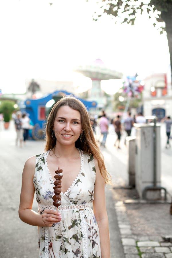 Retrato de la chica joven feliz de la sonrisa hermosa con la fresa en chocolate en el fondo del parque de atracciones imagen de archivo