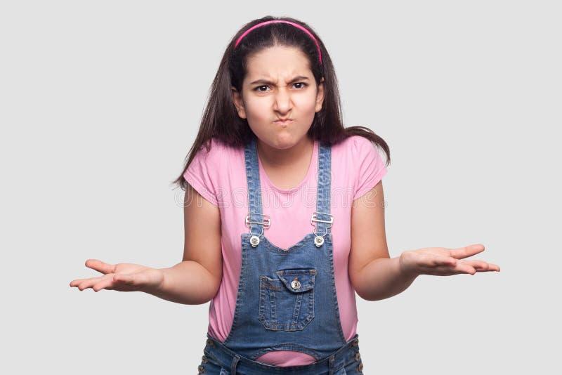Retrato de la chica joven morena confusa en el estilo sport, la camiseta rosada y los guardapolvos azules colocándose con los bra imagen de archivo