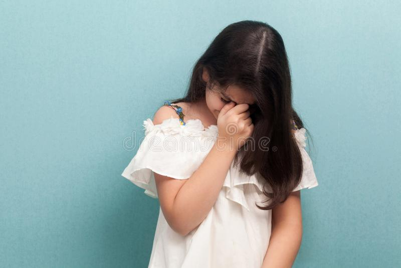 Retrato de la chica joven morena hermosa infeliz triste con el pelo recto largo negro en el vestido blanco que se coloca y que ll imagen de archivo libre de regalías