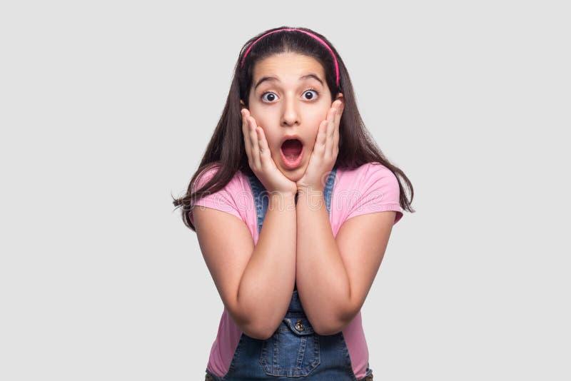 Retrato de la chica joven morena hermosa sorprendida en camiseta rosada casual y los guardapolvos azules que se colocan con las m foto de archivo libre de regalías