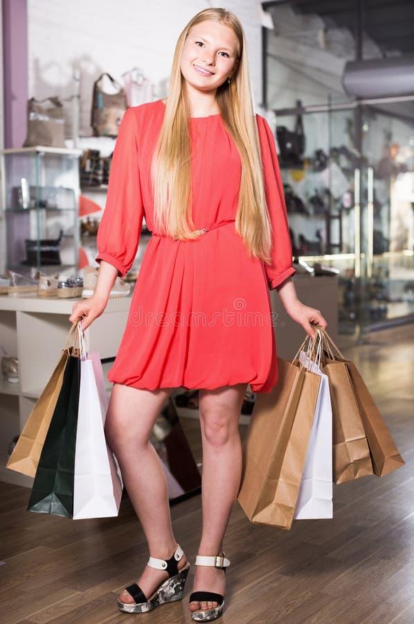 Retrato de la chica joven que está mostrando compras foto de archivo