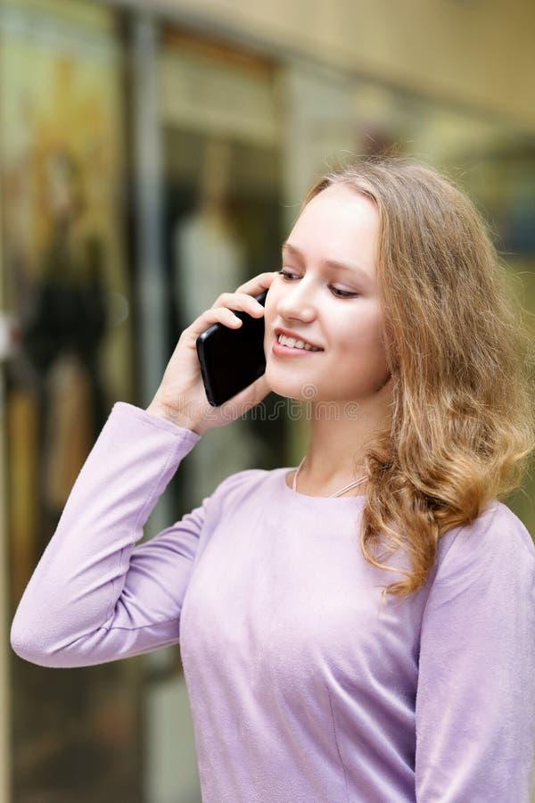 Retrato de la chica joven que habla por el teléfono móvil imagenes de archivo