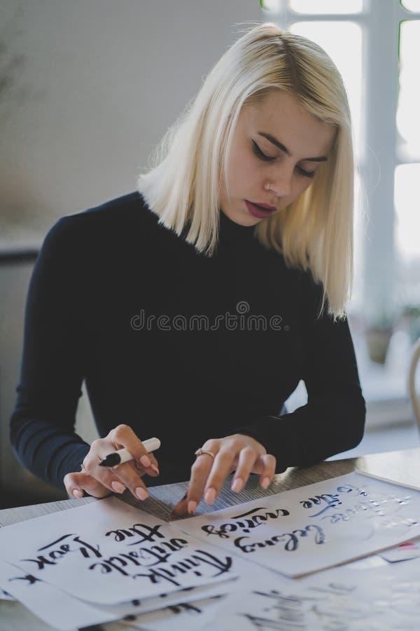 Retrato de la chica joven que se sienta en biblioteca u oficina y que trabaja con las letras en los papeles Mujer rubia con perfe fotografía de archivo