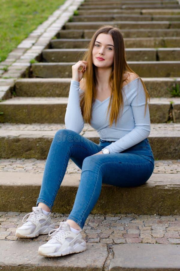 Retrato de la chica joven que se sienta en las escaleras fotografía de archivo libre de regalías