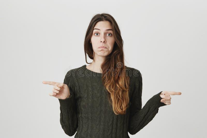 Retrato de la cintura-para arriba de la chica joven atractiva con la expresión triste y decepcionada, señalando los dedos índices imagenes de archivo