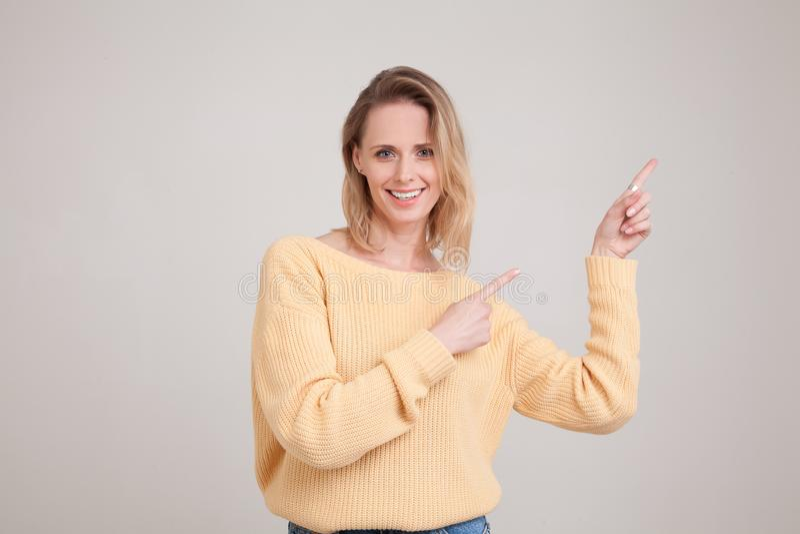 Retrato de la cintura-para arriba de la mujer rubia sonriente feliz que se?ala los fingeres lejos, mostrando algo interesante y l fotos de archivo