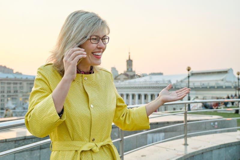 Retrato de la ciudad de la mujer sonriente madura en vidrios, capa amarilla hablando en el tel?fono m?vil, panorama urbano del fo fotos de archivo