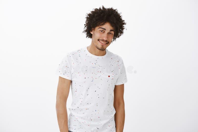 Retrato de la clase encantadora y del modelo masculino hispánico apto con el bigote y el peinado afro, sonrisa coqueta y muy conf imagen de archivo