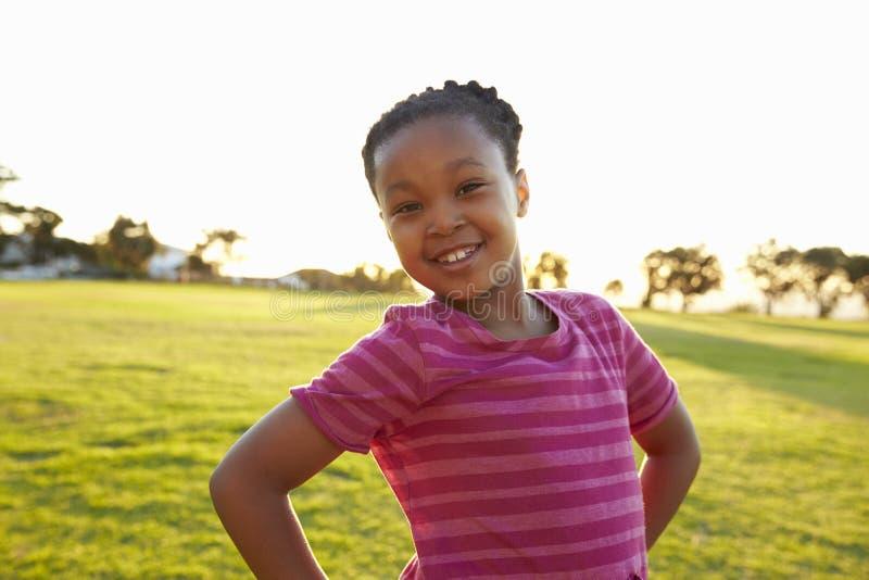 Retrato de la colegiala elemental africana que presenta en un parque fotos de archivo libres de regalías
