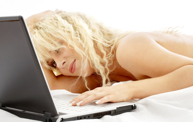 Retrato de la colocación rubia en cama con la computadora portátil fotografía de archivo libre de regalías