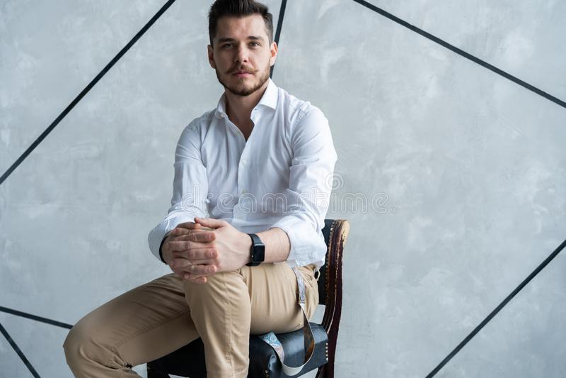 Retrato de la confianza Integral de hombre joven pensativo en el traje lleno que parece ausente mientras que se sienta en el tabu foto de archivo libre de regalías
