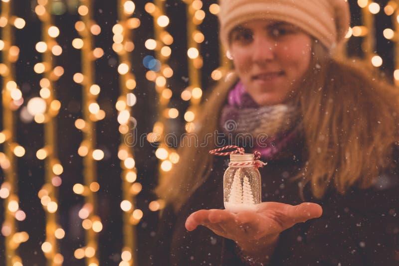 Retrato de la decoración femenina del día de fiesta que se sostiene contra la Navidad imagen de archivo libre de regalías