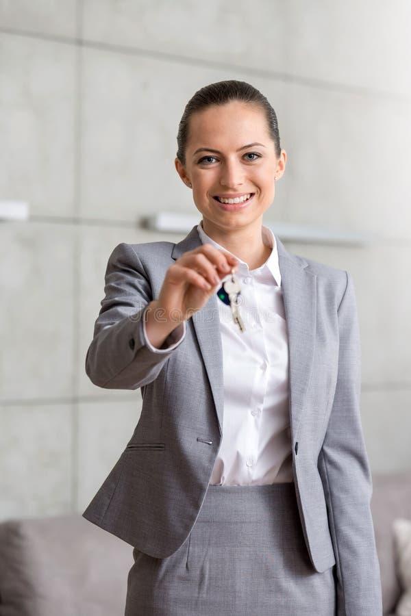 Retrato de la dependienta joven sonriente que da llaves de la casa mientras que se opone a la pared en el apartamento foto de archivo libre de regalías