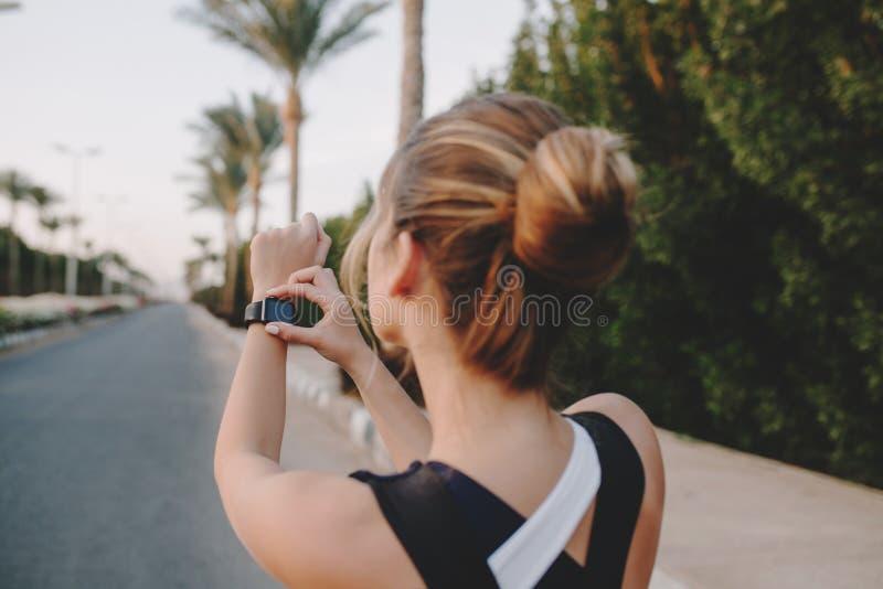 Retrato de la deportista de moda trasera que mira el reloj moderno en las manos en de la calle con las palmeras de tropical foto de archivo libre de regalías