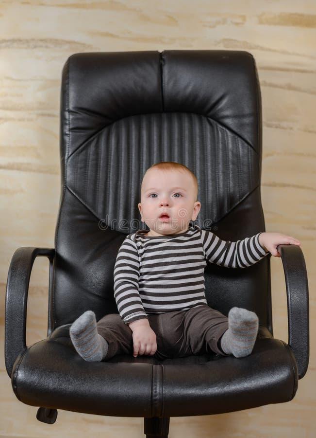 Retrato de la diversión de un muchacho lindo en una silla de la oficina imagenes de archivo