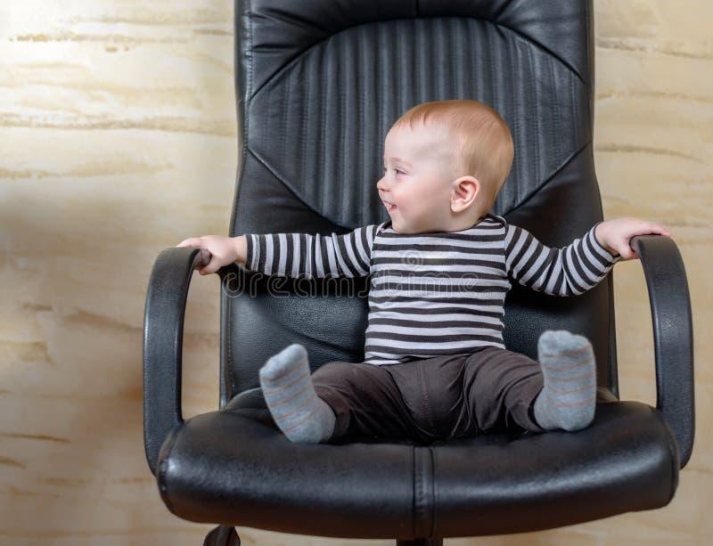 Retrato de la diversión de un muchacho lindo en una silla de la oficina fotografía de archivo