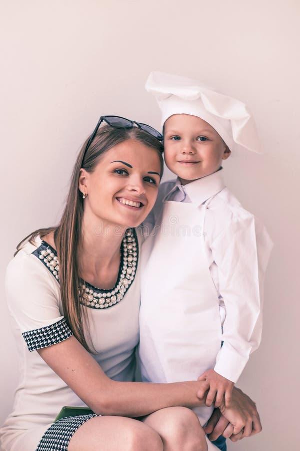 Retrato de la edad temprana feliz de la madre y del ni?o bajo la forma de cocinero fotografía de archivo libre de regalías