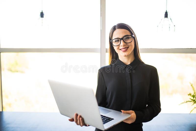 Retrato de la empresaria acertada que sostiene el ordenador portátil en sus manos Mujer confiada hermosa feliz que se coloca en l foto de archivo libre de regalías