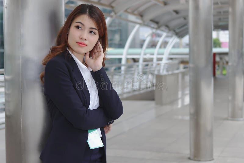 Retrato de la empresaria asiática joven de la belleza en el traje que se coloca y que mira lejos Pensamiento y concepto pensativo foto de archivo