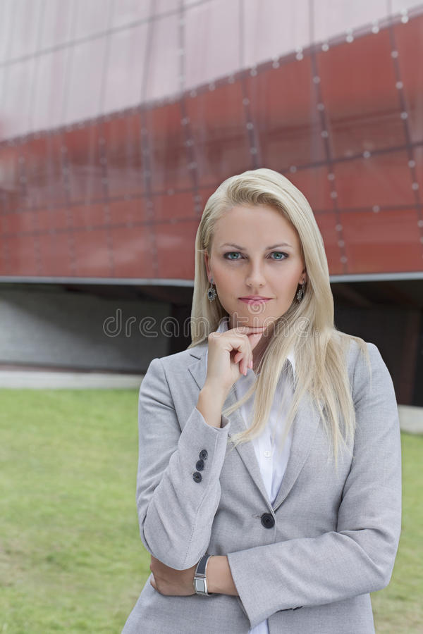 Retrato de la empresaria confiada que se opone con la mano en la barbilla al edificio de oficinas foto de archivo libre de regalías