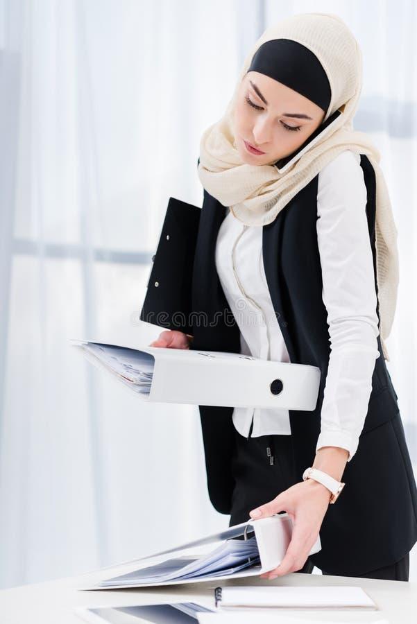 retrato de la empresaria en hijab con los documentos que habla en smartphone foto de archivo