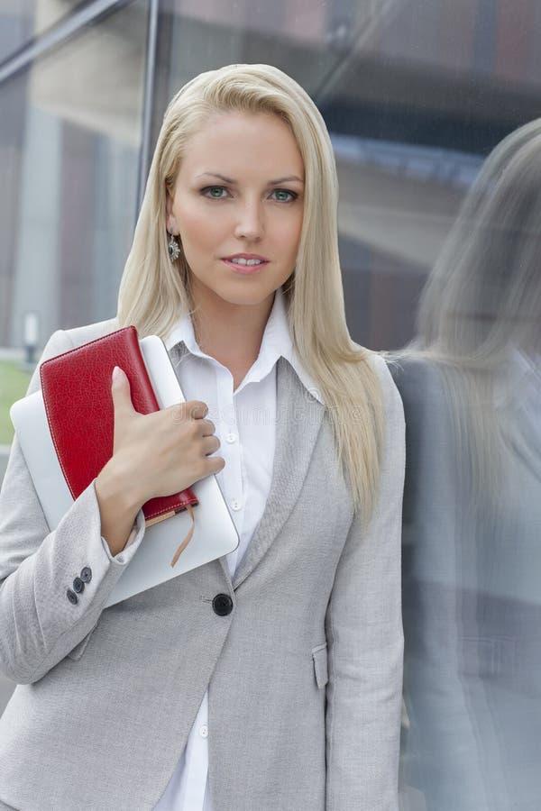 Retrato de la empresaria hermosa que sostiene el organizador y la tableta digital mientras que se inclina en la pared de cristal foto de archivo