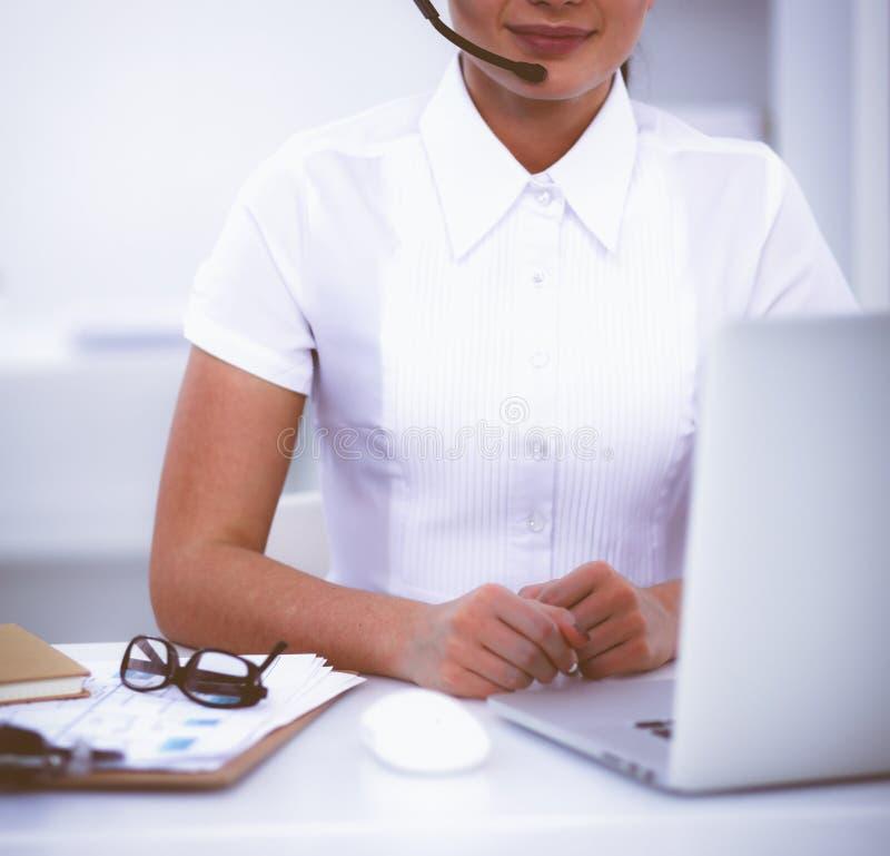 Retrato de la empresaria hermosa que trabaja en su escritorio con las auriculares y el ordenador portátil fotografía de archivo