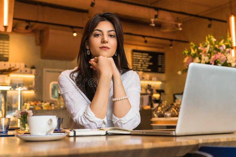 Retrato de la empresaria joven La muchacha trabaja remotamente en el ordenador portátil en restaurante Márketing en línea, educac imagen de archivo