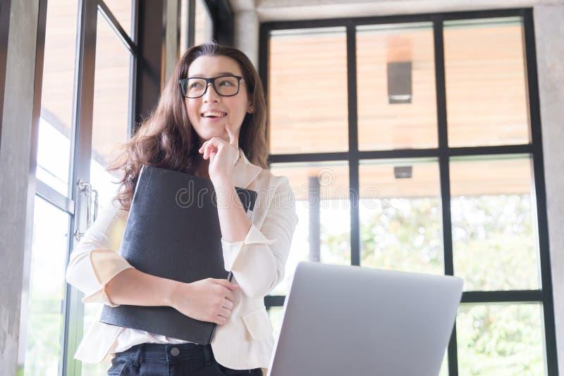 Retrato de la empresaria joven smileing y que lleva a cabo el documento, ?xito en concepto del negocio, del trabajo y de la educa foto de archivo