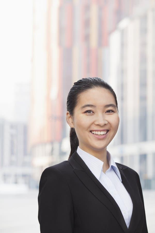 Retrato de la empresaria joven sonriente con una cola de caballo al aire libre con los rascacielos en el fondo, Pekín, China foto de archivo