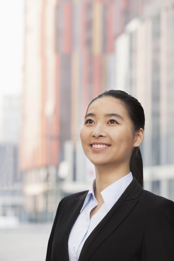 Retrato de la empresaria joven sonriente, mirando para arriba imagenes de archivo