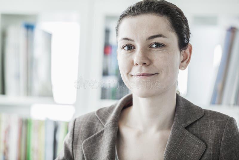 Retrato de la empresaria joven sonriente que mira la cámara, el principal y los hombros imagen de archivo