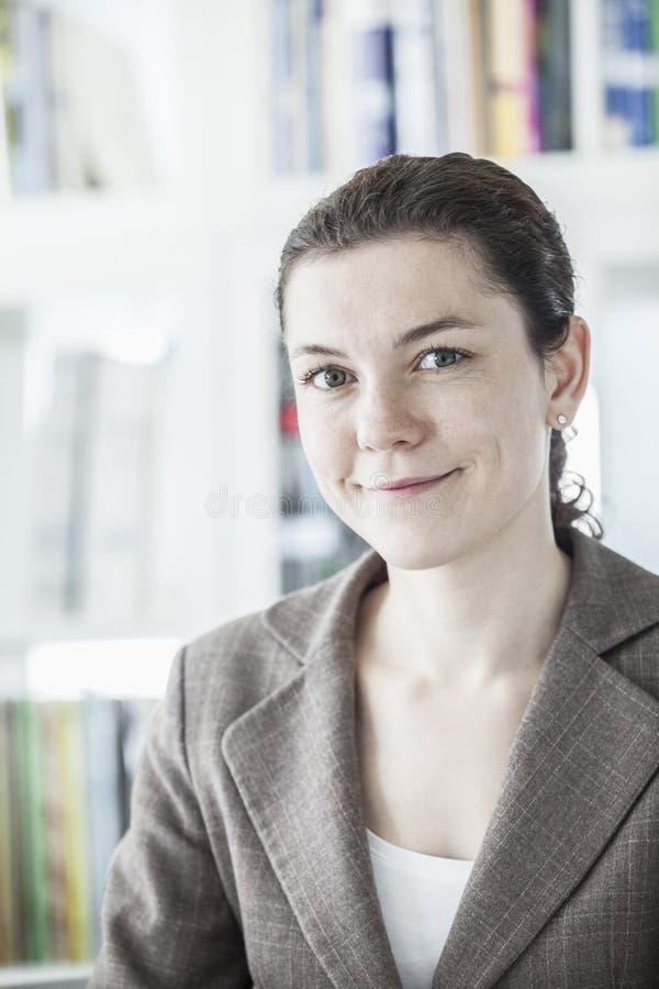 Retrato de la empresaria joven sonriente que mira la cámara, el principal y los hombros imagen de archivo libre de regalías