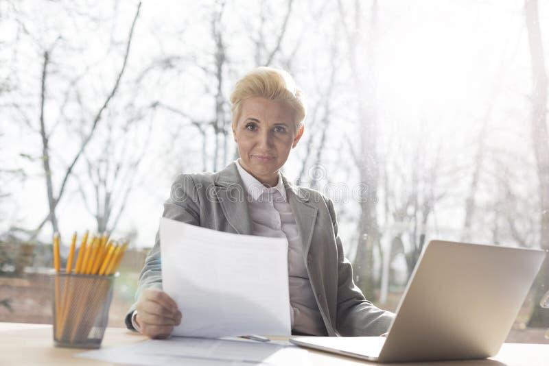 Retrato de la empresaria madura confiada que se sienta con el documento y el ordenador portátil en el escritorio contra ventana e fotografía de archivo libre de regalías