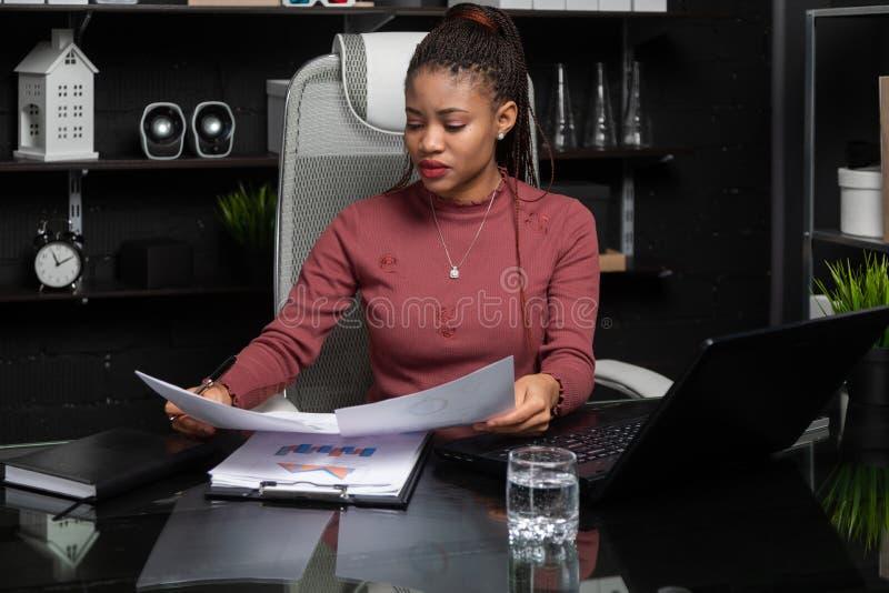 Retrato de la empresaria negra joven que trabaja con las cartas y los diagramas en el escritorio en oficina foto de archivo