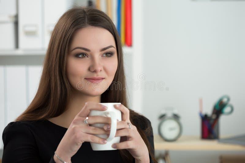 Retrato de la empresaria sonriente joven que se sienta en su oficina fotos de archivo