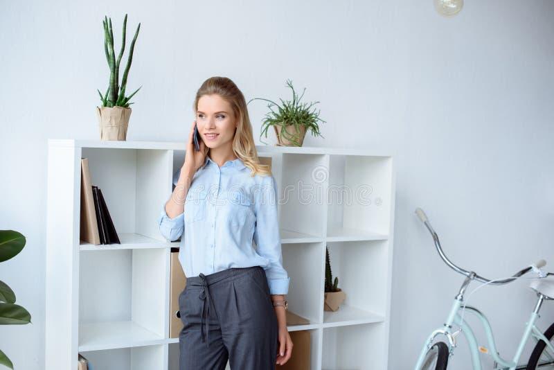 retrato de la empresaria sonriente que habla en smartphone mientras que coloca los estantes cercanos foto de archivo