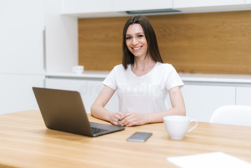 Retrato de la empresaria sonriente que se sienta en oficina y que mira la cámara fotografía de archivo libre de regalías